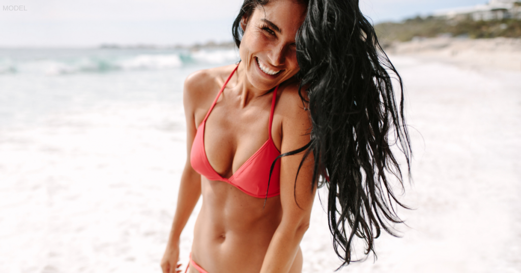 Woman smiling on the beach wearing a bathing suit after CoolSculpting in Boston, MA